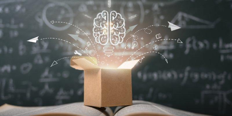 uma caixa de papelão aberta sobre um livro, de onde sai uma luz e vários ícones representando novas ideias