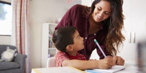 Mãe a ajudar o filho com a lição de casa, sentado na mesa no quarto