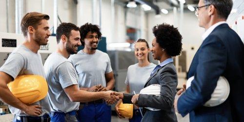 Uma mulher negra de terno aperta a mão de um trabalhador da indústria