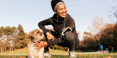 Uma atleta negra pratica atividades físicas feliz em um parque junto com seu cãozinho