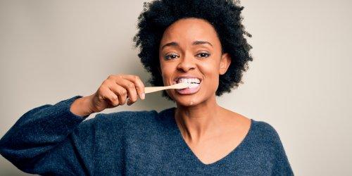 Mulher afro-americana escovando os dentes usando escova de dentes
