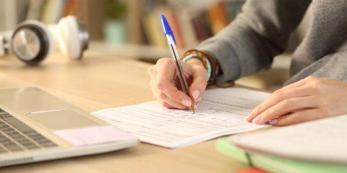Mãos de estudante preenchendo documento de formulário em casa