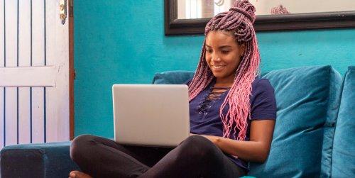 Jovem negra com trança usa um notebook em quarto de casa