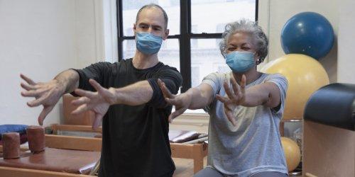 Pessoas fazendo exercício no centro de reabilitação usando máscara