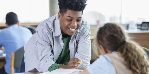 Vê-se um menino negro de camiseta em uma sala de aula, apoiado na mesa de uma colega e conversando com ela sorrindo.